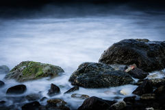 Ghostly Rocks Shoreline. Several type and size of rocks on the shoreling covered with moss with ghostly sea water wandering around them. Shoreline located in the Stock Image