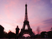 Ghostly tourists surround the Eiffel Tower at night Stock Image