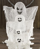 Ghosts family vertical. Halloween still life with four ghosts with chains on wood Stock Photo