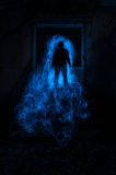 Ghosts in the garden. A ghostly human figure on top of stairs, just under a door frame that gives access to a very dark room. The ghost is overlooking the garden Stock Images