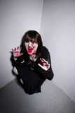 Ghoul in a Corner. Young female zombie or vampire in a corner Stock Photo