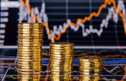 Giù pile di tendenza di monete dorate e di grafico finanziario fotografia stock