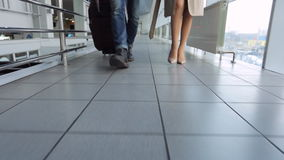 Giù vista delle coppie che camminano giù il corridoio dell'aeroporto archivi video