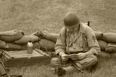 GI in Field. Reading, PA, USA - June 6, 2015 :  Sepia image of a WWII American GI in a trench Royalty Free Stock Image