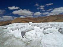 Giacimenti bianchi del sale, una montagna enorme di sale nella priorità alta, dietro le nuvole ed il cielo blu montagnosi, Ladakh Fotografia Stock Libera da Diritti