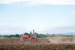 Giacimento d'aratura del trattore rosso Fotografia Stock Libera da Diritti