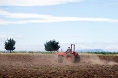 Giacimento d'aratura del trattore rosso Immagine Stock