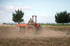 Giacimento d'aratura del trattore rosso Immagini Stock