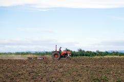 Giacimento d'aratura del trattore rosso Immagine Stock Libera da Diritti