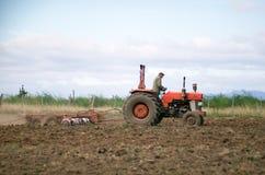 Giacimento d'aratura del trattore rosso Fotografie Stock