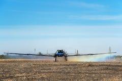 Giacimento d'innaffiatura del trattore all'azienda agricola Immagini Stock