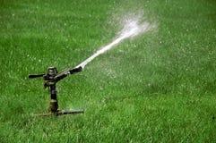 Giacimento d'innaffiatura dello spruzzatore di erba verde Fotografie Stock