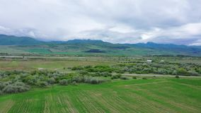 Giacimento della primavera vicino alle montagne Cielo nuvoloso stock footage