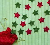 Giacimento detritico delle stelle rosse e verdi e della borsa rossa del regalo Immagine Stock Libera da Diritti