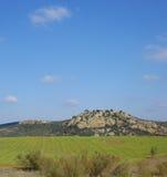 Giacimento di grano accanto alle montagne e un cielo blu con il fondo delle nuvole Fotografia Stock