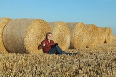 Giacimento di grano d'esame dell'agricoltore dopo il raccolto facendo uso della compressa Fotografie Stock