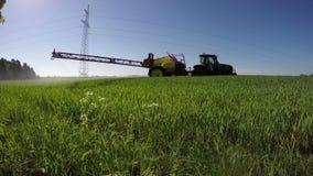 Giacimento di grano di spruzzatura del trattore con l'antiparassitario dell'insetticida del diserbante in primavera video d archivio