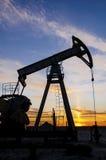 Giacimento di petrolio durante il tramonto Immagini Stock