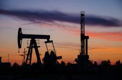 Giacimento di petrolio durante il tramonto Fotografia Stock