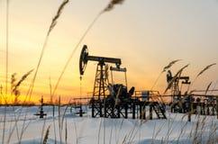 Giacimento di petrolio durante il tramonto nell'orario invernale Immagini Stock Libere da Diritti
