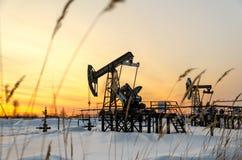 Giacimento di petrolio durante il tramonto nell'orario invernale Fotografia Stock Libera da Diritti