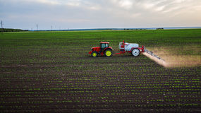 Giacimento di spruzzatura del trattore alla molla Fotografia Stock Libera da Diritti