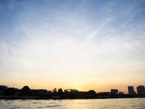 Giallo del cielo del sole di mattina nel fiume della città immagini stock libere da diritti