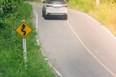 ` Giallo di traffico del labirinto del ` del segnale stradale sul cespuglio verde accanto alla strada con il fondo di luce solare Fotografia Stock