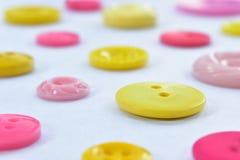 Giallo e bottoni di cucito rosa su bianco Fotografia Stock Libera da Diritti