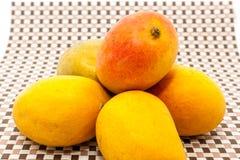 Giallo maturo ed il rosso hanno colorato i frutti del mango sul fondo della stuoia Immagini Stock