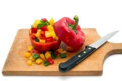 Giallo tagliato, rosso e peperoni verdi e un coltello da cucina su un bordo di legno Immagini Stock Libere da Diritti