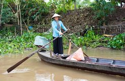 An Giang,越南- 2014年11月29日:农村妇女在连队河,湄公河荡桨旅游业小船三角洲,越南南方 有更多和 免版税库存照片