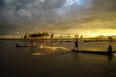 An Giang,越南- 2016年12月6日:在培养的领域的日落与抓鱼的渔夫通过投掷巢在Chau Doc, An Giang, s 库存图片