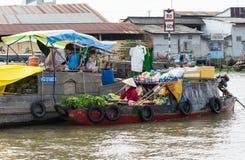 An Giang,越南- 2014年11月30日:当地人民卖果子和每日主要物品在划船或汽艇在浮动市场上在ri 免版税图库摄影