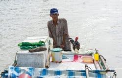 An Giang,越南- 2014年11月30日:有他的公鸡的一个人在汽艇在湄公河三角洲河  公鸡是为卖给某人wh 免版税库存图片