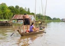 An Giang, Вьетнам - 29-ое ноября 2014: Семья двигая весельной лодкой, самая общая середина транспорта сельских жителей в Меконге  стоковое фото