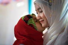 An Giang, Vietnam - 6 de septiembre de 2016: Muchacha musulmán vietnamita que lleva el vestido rojo tradicional que juega con su  Foto de archivo libre de regalías