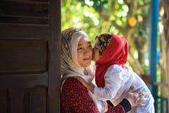 An Giang, Vietnam - 6 de septiembre de 2016: Muchacha musulmán vietnamita que lleva el vestido rojo tradicional que juega con su  Fotografía de archivo libre de regalías