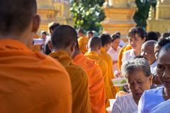 An Giang, Vietnam - Dec 6, 2016: Buddhist monk in south of Vietnam stand in a row waiting people put rice and food offerings in th. Eir alms bowl Royalty Free Stock Image