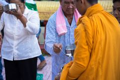 An Giang, Vietnam - Dec 6, 2016: Buddhist monk in south of Vietnam stand in a row waiting people put rice and food offerings in th. Eir alms bowl Royalty Free Stock Photo