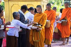 An Giang, Vietnam - Dec 6, 2016: Buddhist monk in south of Vietnam stand in a row waiting people put rice and food offerings in th. Eir alms bowl Royalty Free Stock Images