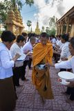 An Giang, Vietnam - Dec 6, 2016: Buddhist monk in south of Vietnam stand in a row waiting people put rice and food offerings in th. Eir alms bowl in Chau Doc Stock Photos