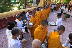 An Giang, Vietnam - Dec 6, 2016: Buddhist monk in south of Vietnam stand in a row waiting people put rice and food offerings in th. Eir alms bowl in Chau Doc Royalty Free Stock Image