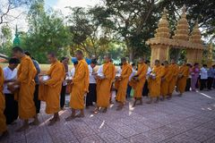 An Giang, Vietnam - Dec 6, 2016: Buddhist monk in south of Vietnam stand in a row waiting people put rice and food offerings in th. Eir alms bowl in Chau Doc Stock Photo