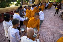 An Giang, Vietnam - Dec 6, 2016: Buddhist monk in south of Vietnam stand in a row waiting people put rice and food offerings in th. Eir alms bowl in Chau Doc Stock Image