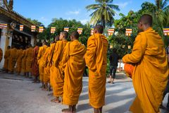 An Giang, Vietnam - Dec 6, 2016: Buddhist monk in south of Vietnam stand in a row waiting people put rice and food offerings in th. Eir alms bowl in Chau Doc Stock Photography