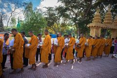 An Giang, Vietnam - Dec 6, 2016: Buddhist monk in south of Vietnam stand in a row waiting people put rice and food offerings in th. Eir alms bowl in Chau Doc Royalty Free Stock Photography