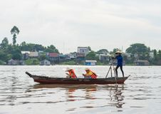 An Giang, Vietnam - Nov 29, 2014: Tourists carried by rowing boat on Tien river, Mekong delta. They enjoying cellphone instead of. Seeing beautiful scene around Stock Images