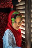 An Giang, Vietnam - Sep 6, 2016: Portrait of Vietnamese muslim little girl wearing traditional red dress in a champa village, Khan. H Hoan district, South Stock Image