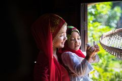 An Giang, Vietnam - Sep 6, 2016: Vietnamese muslim girl wearing traditional red dress playing with her sister in a champa village,. Khanh Hoan district, South Royalty Free Stock Image
